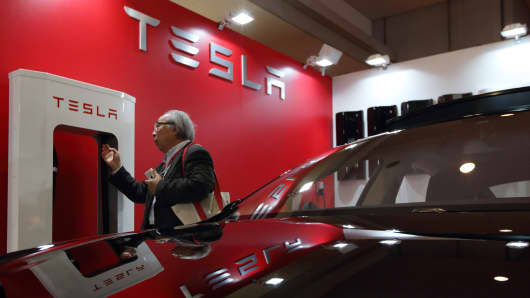 A man looks at a battery charger near a Tesla Motors Model S electric vehicle.