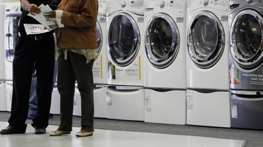 A customer talks to a sales associate in front of a row of Whirlpool washing and drying machines.