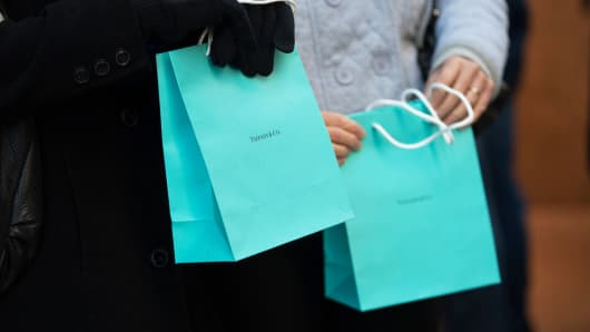 Customers carry Tiffany & Co. shopping bags outside the company's flagship store in New York, March 18, 2014.