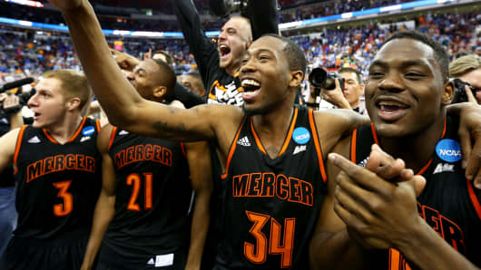 Jibri Bryan #34 of the Mercer Bears celebrates with teammates after defeating the Duke Blue Devils 78-71 during the Second Round of the 2014 NCAA Basketball Tournament at PNC Arena on March 21, 2014 in Raleigh, North Carolina.
