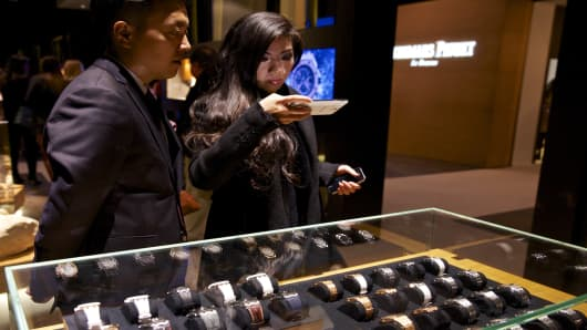 Visitors look at a display of luxury wristwatches manufactured by Audemars Piguet at the Salon International de la Haute Horlogerie (SIHH) watch fair in Geneva, Switzerland.
