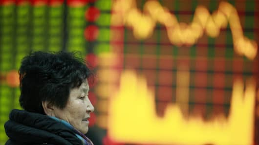A woman sits at a securities exchange in Huaibei, central China's Anhui province.