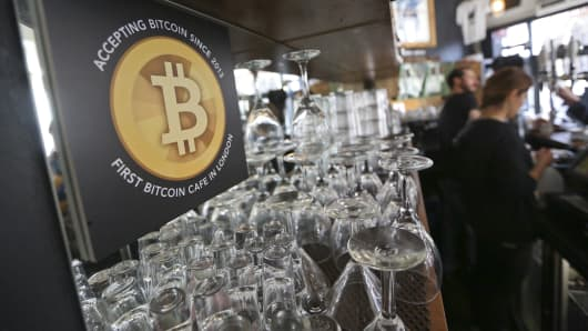 A poster alerting customers that the digital currency Bitcoin is accepted as payment sits behind the counter inside the Old Shoreditch Station cafe in London, U.K..