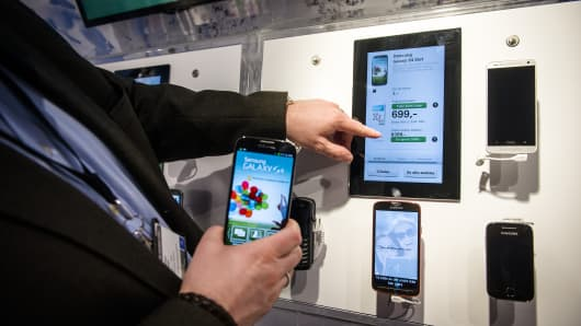 An employee demonstrates smartphones manufactured by Samsung Electronics Co. at the Stroemmen shopping mall in Norway.