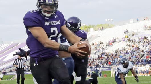 "Northwestern University quarterback Kain Colter, No. 2, wears APU for ""All Players United"" on wrist tape as he scores a touchdown during an NCAA football game against Maine in Evanston, Ill."