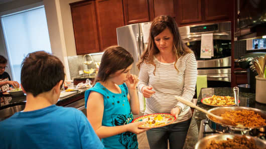 Alice Korey, right, serves dinner with her daughter, Elana, 10, who helped her cook, and her son Luke, 9, at their home in Katy, Texas, March 27, 2014.