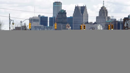 Cars drive down Grand River Avenue in Detroit with the city's skyline in the background.