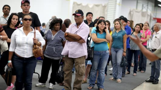 People stand in the line to register to meet with Sunshine Life & Health Advisors, which is selling insurance under the Affordable Care Act at a store setup in the Mall of the Americas on March 31, 2014, in Miami.