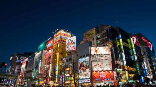 Commercial buildings and retail stores stand illuminated at night in the district of Akihabara in Tokyo, Japan.