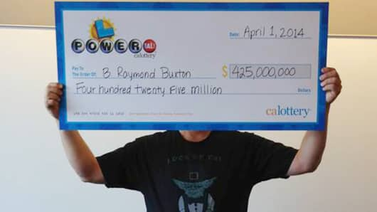 Powerball winner B. Raymond Buxton holding a check for $425 million, Tuesday, April 1, 2014, in Sacramento, California.