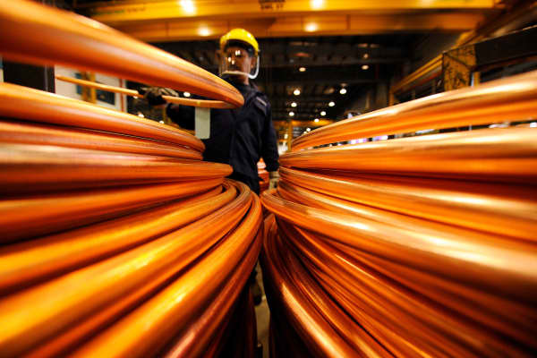 An employee inspects coils of copper rod.