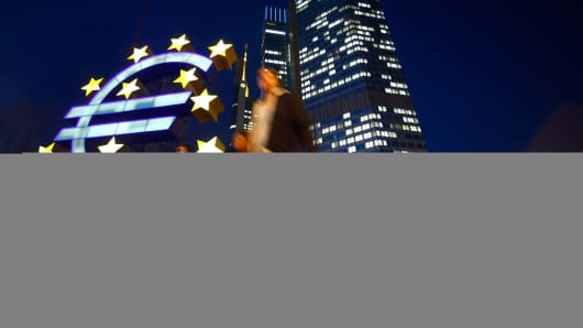 Pedestrians pass a euro sign sculpture outside the headquarters of the European Central Bank in Frankfurt.