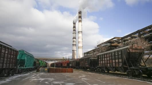 Power plant chimneys stand beside a freight wagon yard at United Co. Rusal's alumina