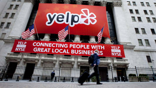 A Yelp banner and sign hang outside the New York Stock Exchange building.