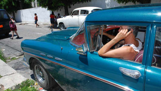 A Cuban man uses his mobile phone in a car in Havana.