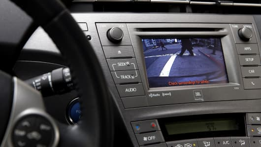 Pedestrians are displayed on the video display of a backup camera on a Toyota Prius in San Francisco.