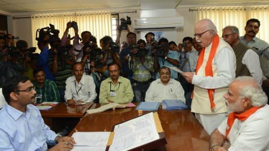 India's Bharatiya Janata Party (BJP) leader L.K. Advani (2nd R) reads out his nomination ahead of elections which kicked off on April 7.
