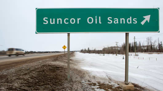 A sign directing traffic to the Suncor Oil Sands, north of Fort McMurray, Alberta, Canada.