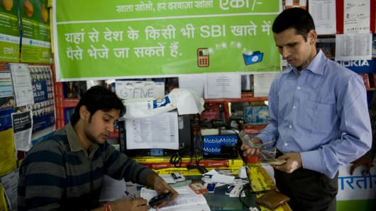 A shopkeeper (L) transfers money for customers using text commands on a mobile phone in New Delhi.