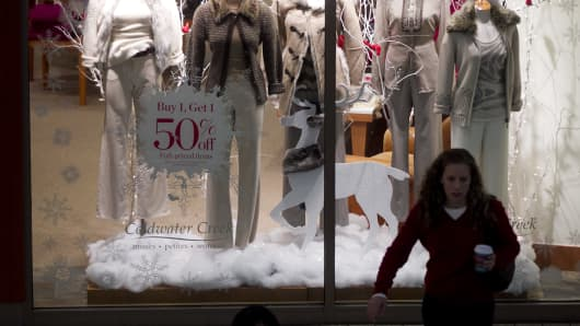 A woman drinks coffee in front of mannequins in the window display of a Coldwater Creek store at the Fair Oaks Mall in Fairfax, Virginia.