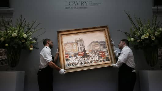 A Sotheby's employees re-hang LS Lowry's painting 'Piccadilly Circus, London' in London, England.