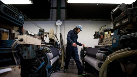 A man works a weaving machine at the Momotaro Jeans factory in Kojima district on February 25, 2014 in Kurashiki, Japan.