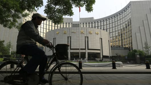 A cyclist rides past the People's Bank of China in Beijing.