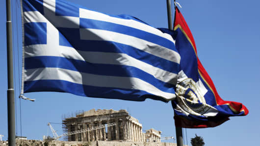 A Greek national flag, left, flies outside the Parthenon temple, on Acropolis hill, in Athens, Greece.