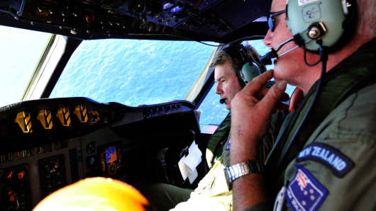 Royal New Zealand Air Force Co-pilot squadron Leader Brett McKenzie (L) and Flight Engineer Trent Wyatt sit in the cockpit aboard a search aircraft as it flies over the southern Indian Ocean looking for debris from missing Malaysian Airlines flight MH370 on April 11, 2014