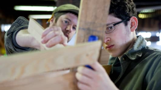 An apprentice works on a whaleboat under the supervision of a boat builder.