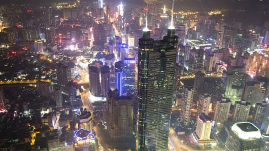 Commercial and residential buildings stand illuminated at night in the Luohu district of Shenzhen, China.