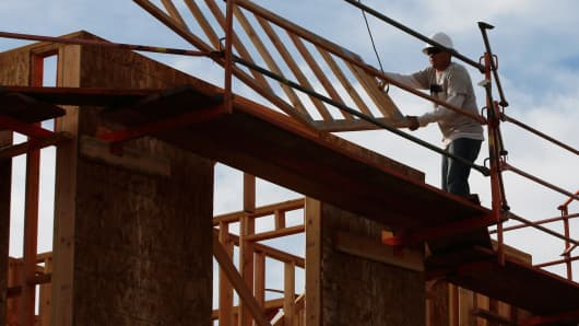 A worker guides a section of a new home into place at the Toll Brothers Baker Ranch community development in Lake Forest, California, Feb. 11, 2014.