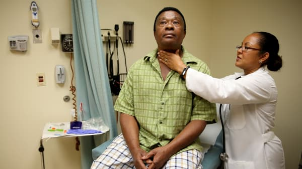 A man who is insured under an insurance plan through the Affordable Care Act receives a checkup from Dr. Peria Del Pino-White at the South Broward Community Health Services clinic on April 15, 2014 in Hollywood, Florida.