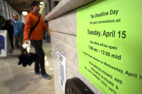 A sign states business hours in the James A. Farley post office in Manhattan, which is open late today, the last day to file taxes on April 15, 2014.