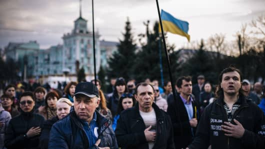 People sing the Ukrainian national anthem during a pro-Ukraine rally in the eastern Ukrainian city of Lugansk.