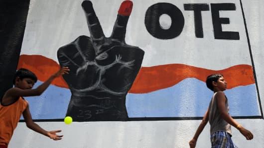 Children walk past an Indian voter awareness mural in Mumbai.