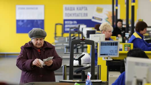 A customer counts ruble banknotes to pay for goods at a Lenta supermarket in Moscow, Russia.