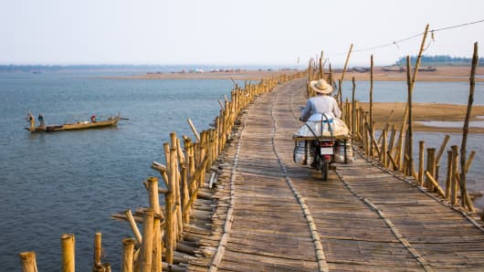A motorbike crossing a bamboo bridge across the Mekong River in Kompong Cham, Cambodia.