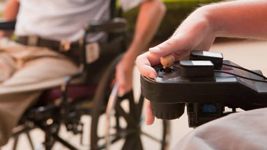 A patient with Duchenne muscular dystrophy controls a motorized wheelchair. DMD afflicts about 1 in 3,500 boys worldwide.