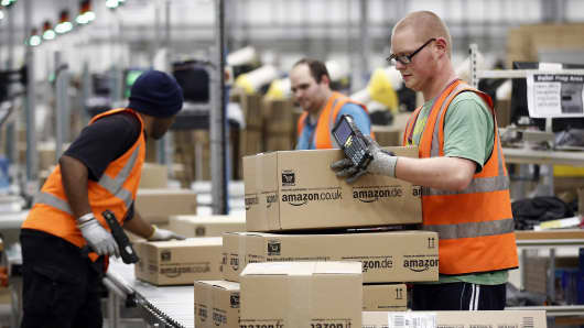 Employees collect packaged customer orders from a conveyor belt ahead of shipping at one of Amazon.com Inc.'s fulfillment centers in Rugeley, U.K.