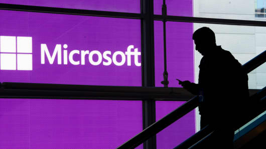 An attendee is silhouetted against a Microsoft poster at the Microsoft Developers Build Conference in San Francisco, April 2, 2014.