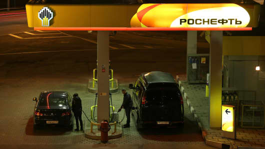 Drivers refuel their vehicles at gas pumps at an OAO Rosneft gas station illuminated at night in Moscow. Investors have dumped $70 billion in assets this year as President Vladimir Putin annexed Crimea and massed troops on Ukraine's border, fueling a reprise of Cold War tensions and concern that sanctions could push Russia into a recession.