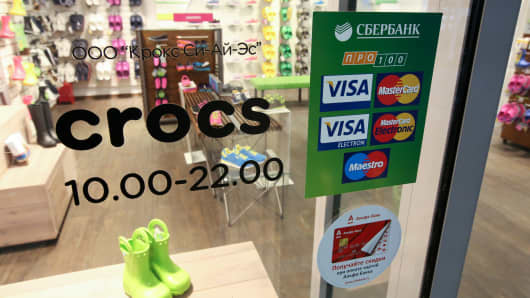 A sign advertising Visa and Mastercard payment services sits in the window of a Crocs shoe store inside the Okhotny Ryad shopping mall in Moscow.
