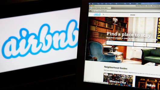 The Airbnb logo and website are displayed on laptop computers in this arranged photograph.