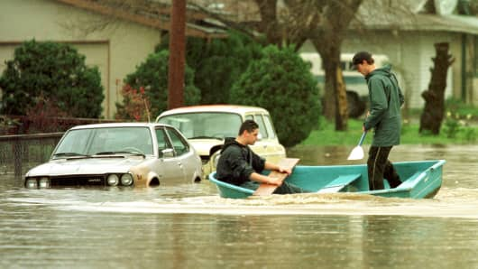 Residents of Petaluma, California, paddle through their neighborhood in February 1998, after El Nino storms caused flooding and mudslides in Northern California.