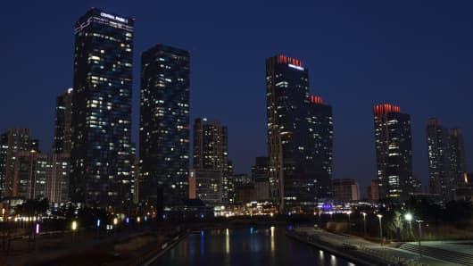 Residential buildings stand illuminated at dusk facing Central Park in the Songdo district of Incheon, South Korea.