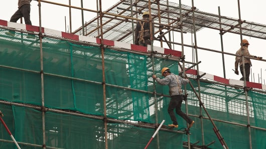 Workers stand on scaffolding during the construction of a new building in Baiyun district, Guangzhou, Guangdong province, China.