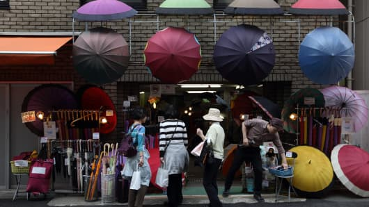 Women shop for umbrellas at a store in Tokyo, Japan.