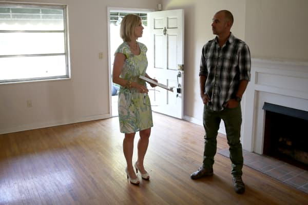 Real estate agent, left, shows a home to a prospective buyer in Coral Gables, Florida.