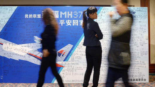 People walk past a billboard in support of missing Malaysia Airlines flight MH370 as Chinese relatives of passengers on the missing Malaysia Airlines flight MH370 have a meeting at the Metro Park Hotel in Beijing.